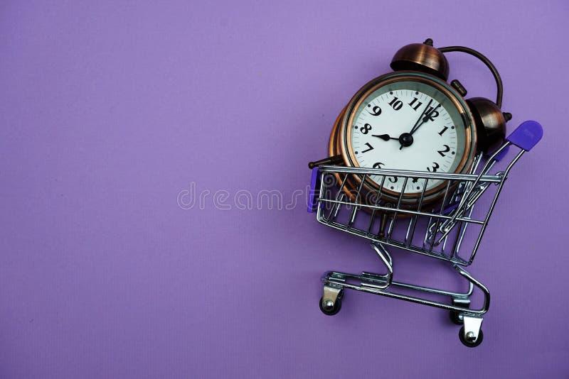 闹钟和微型台车推车有空间拷贝的在紫色背景 免版税库存图片