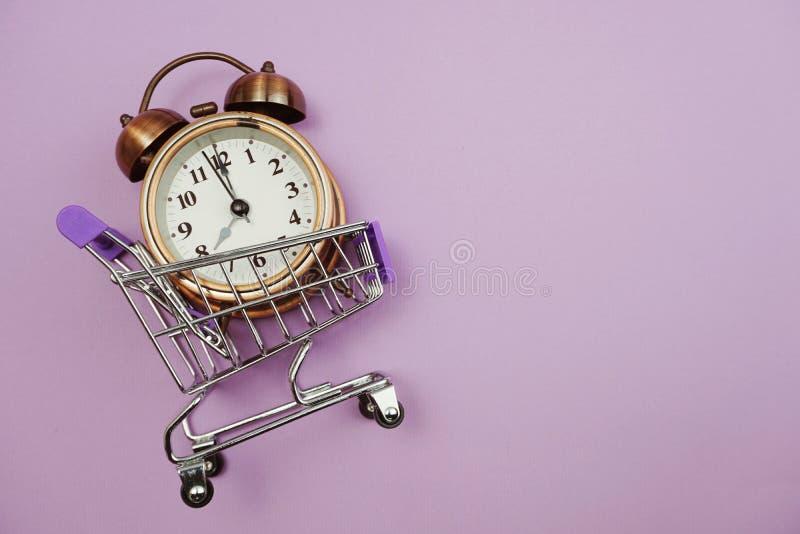 闹钟和微型台车推车有空间拷贝的在紫色背景 免版税库存照片