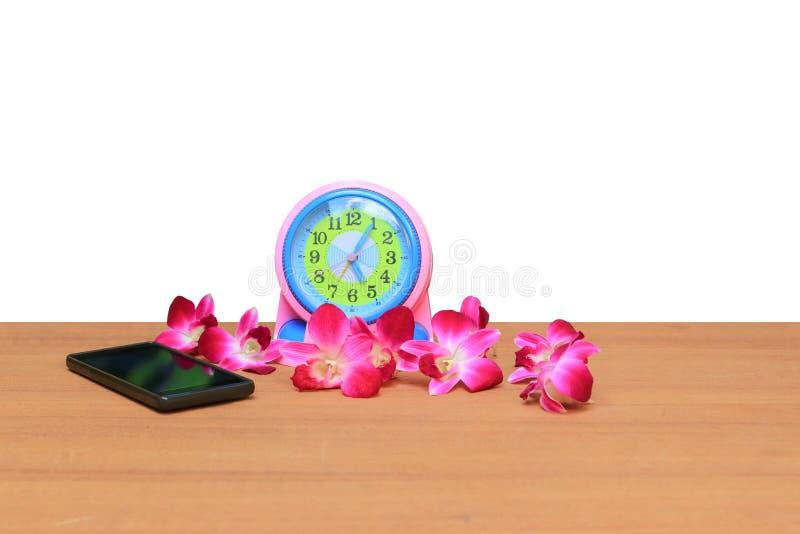 闹钟和手机,紫色兰花在白色背景春天概念的木头开花 免版税库存照片