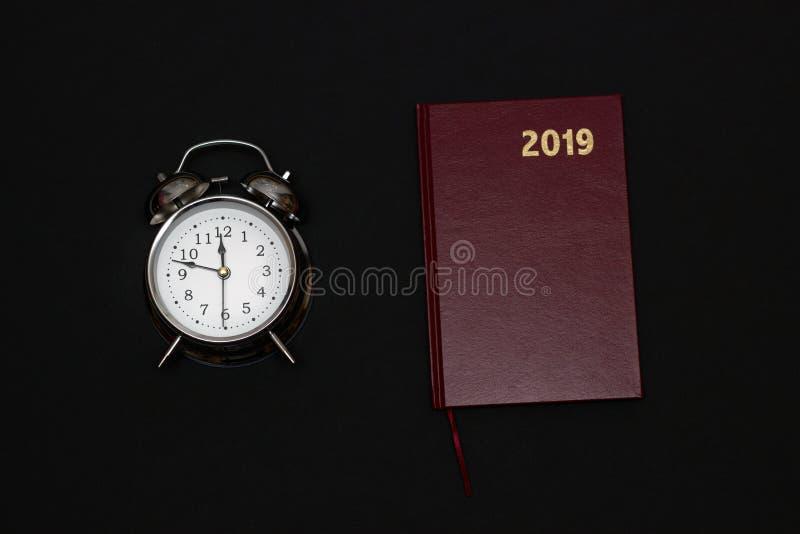 闹钟和笔记本在黑背景, 2019年 免版税库存照片