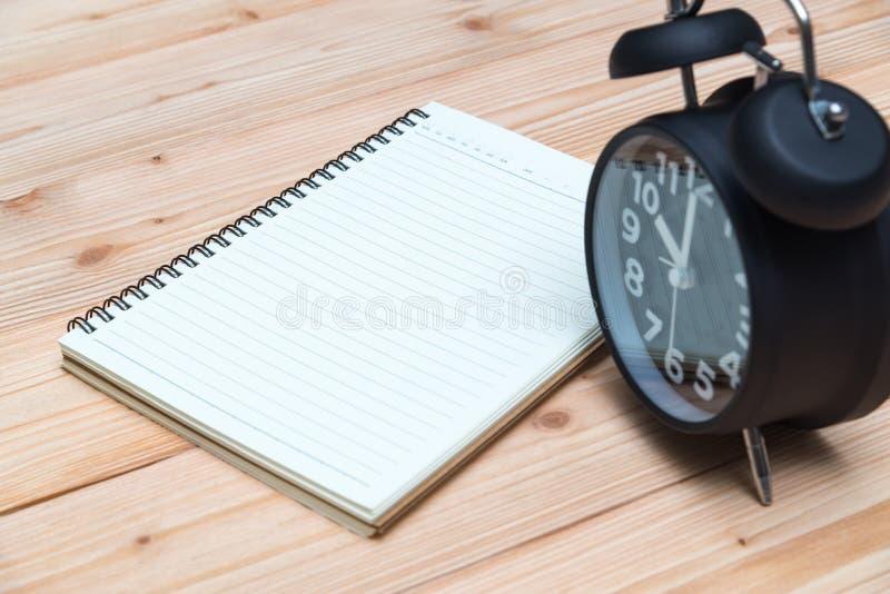 闹钟和笔记本有笔的在木地板,空的空间f上 库存照片