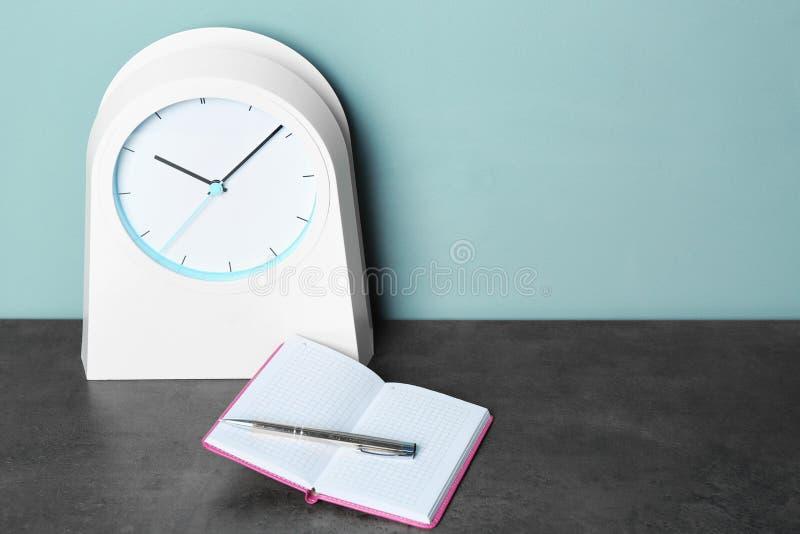 闹钟和笔记本有笔的在桌上 E 库存图片