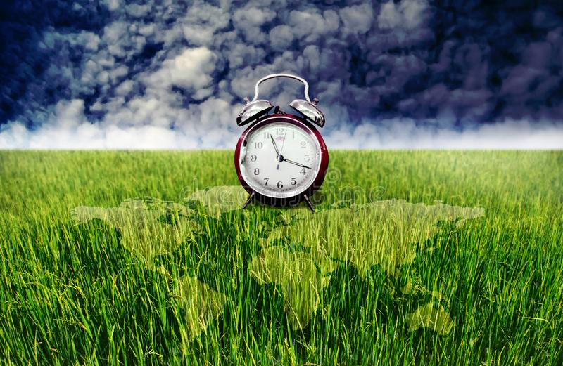 闹钟和绿色米领域与世界地图覆盖物,时间对种植园 免版税库存图片