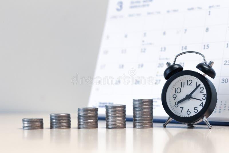 闹钟和金钱硬币堆积有日历背景,攒钱 库存图片