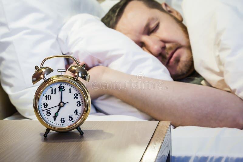 闹钟在一个床头柜上站立在屋子或旅馆客房里 免版税库存照片