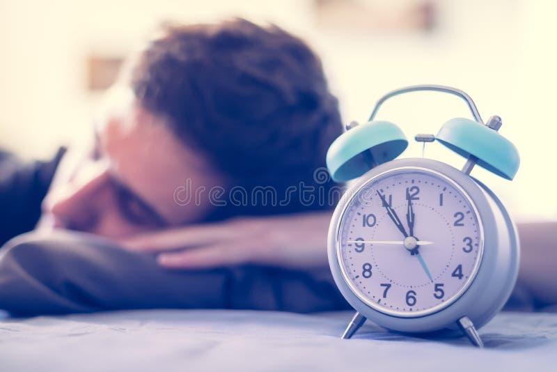 闹钟早晨 年轻人在模糊的背景中睡觉 免版税图库摄影