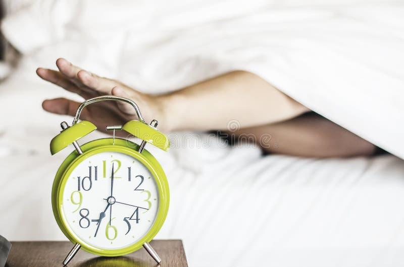 闹钟清早之前打扰的睡觉的亚洲年轻男性 免版税库存图片