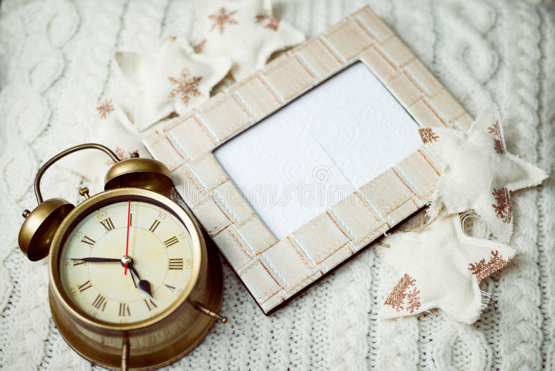 闹钟的图象在被编织的背景的sorounded与装饰星 免版税库存图片