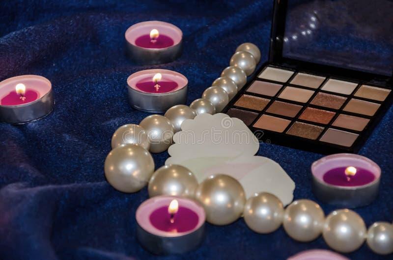 闻的蜡烛、阴影调色板,心脏和美丽的小珠在毯子 库存图片