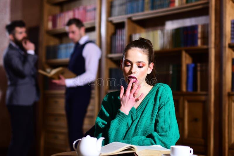 阅读书和研究诗歌 妇女在图书馆读了书在从杯子的茶壶饮用的咖啡 与逗人喜爱的文学咖啡馆 库存图片