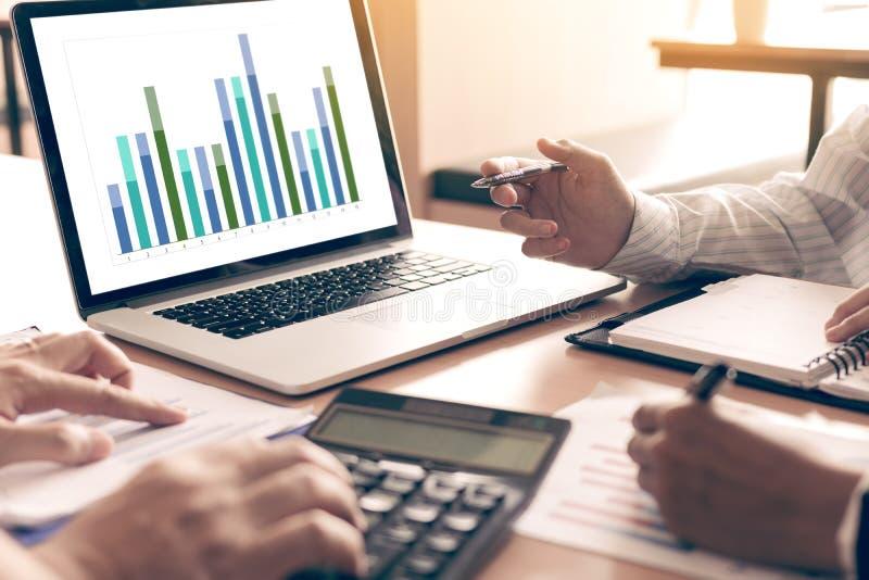 队商人分析在膝上型计算机的综合报告图表在办公室屋子里 免版税库存图片