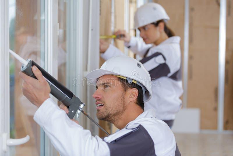 队安装窗口的建筑工人在房子 免版税库存照片