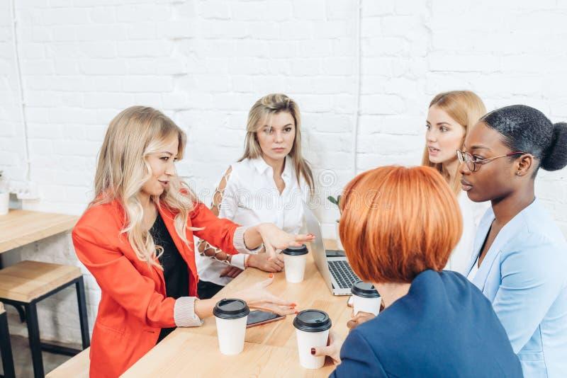 队工作过程 coloborating在露天场所办公室的多种族小组妇女 库存图片