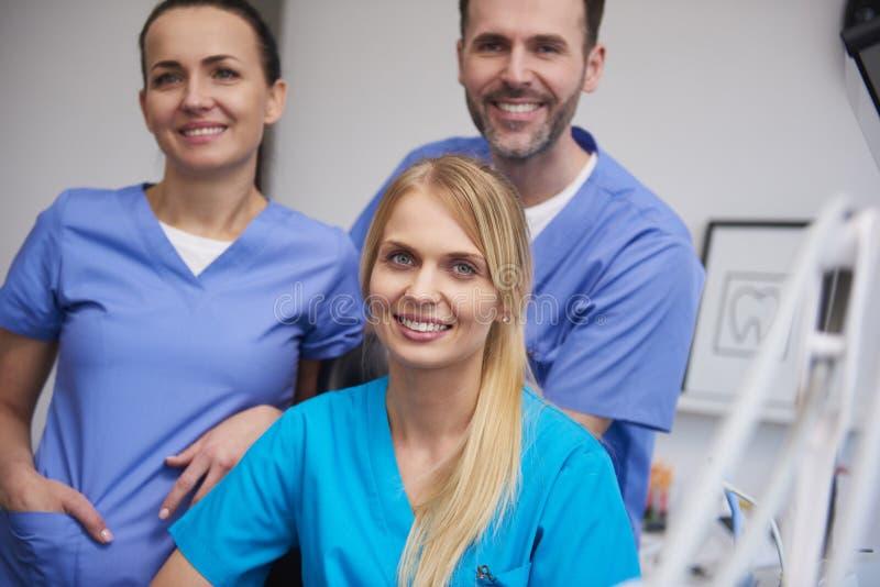 队微笑和满意的牙医在牙医的办公室 免版税图库摄影
