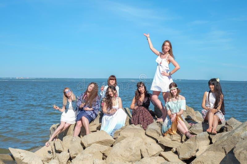 队或小组很美丽的年轻成人少妇在海滩的石头站立,当举行透明玻璃与时 免版税库存图片