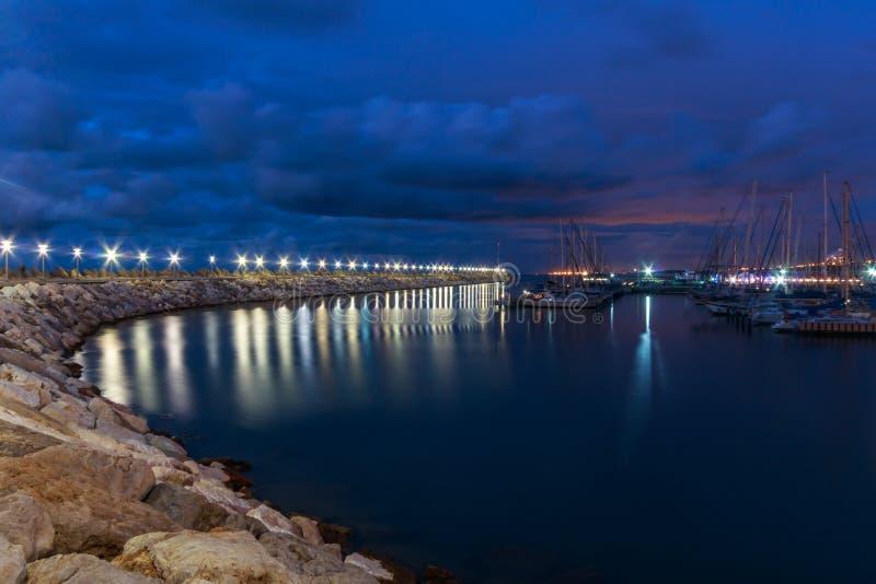 防堤,在水的光在夜阴云密布在小游艇船坞 亚实基伦 以色列 免版税库存图片
