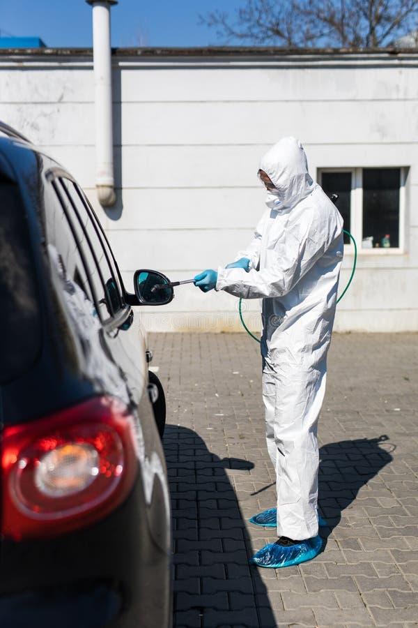 防护服中的消毒剂对汽车污染区进行消毒,以防冠状病毒 保健 免版税库存照片