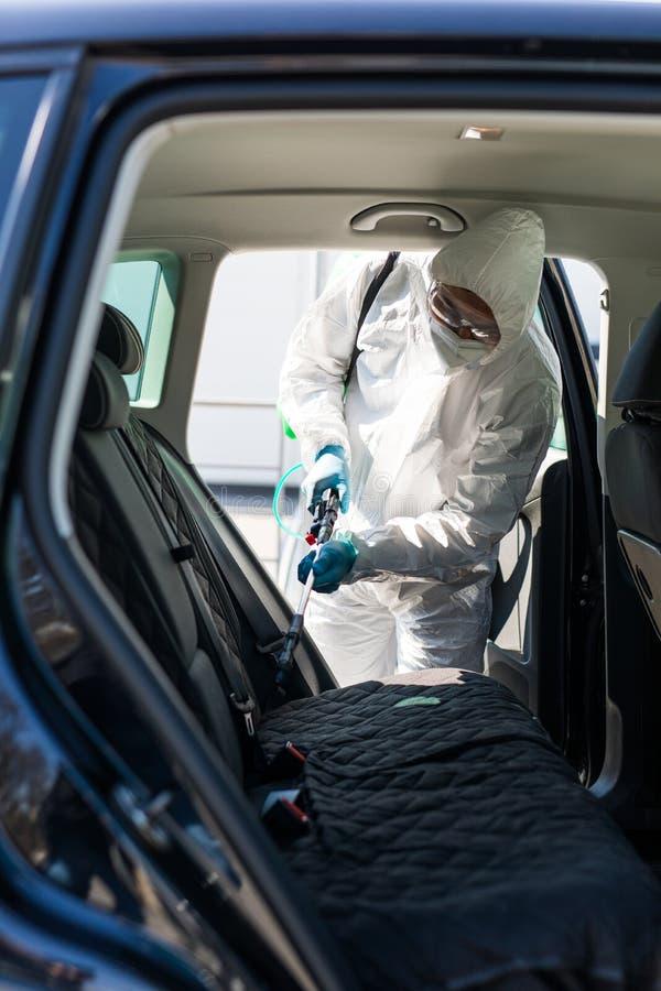 防护服中的消毒剂对汽车污染区进行消毒,以防冠状病毒 保健 库存照片