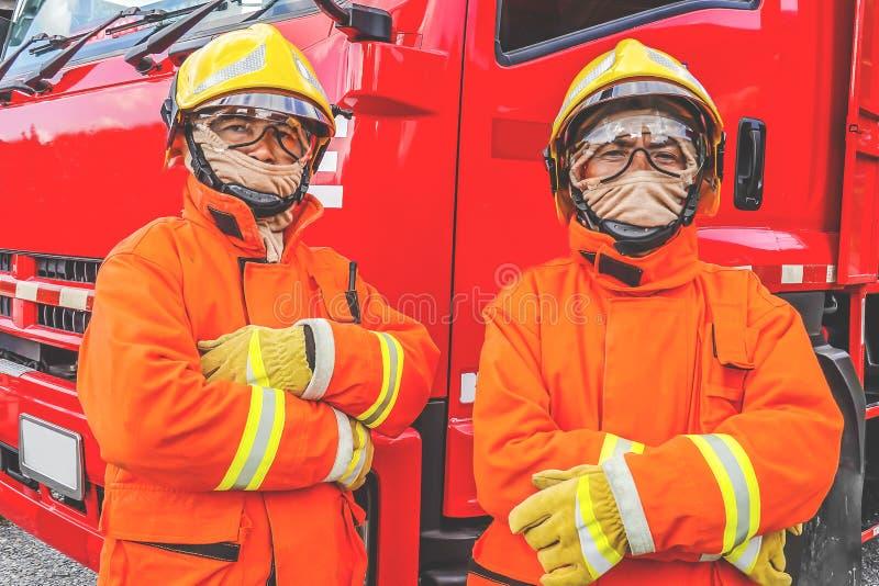 防护服装、盔甲和面具的两名消防队员反对摆在反对消防车背景的消防车 免版税库存图片