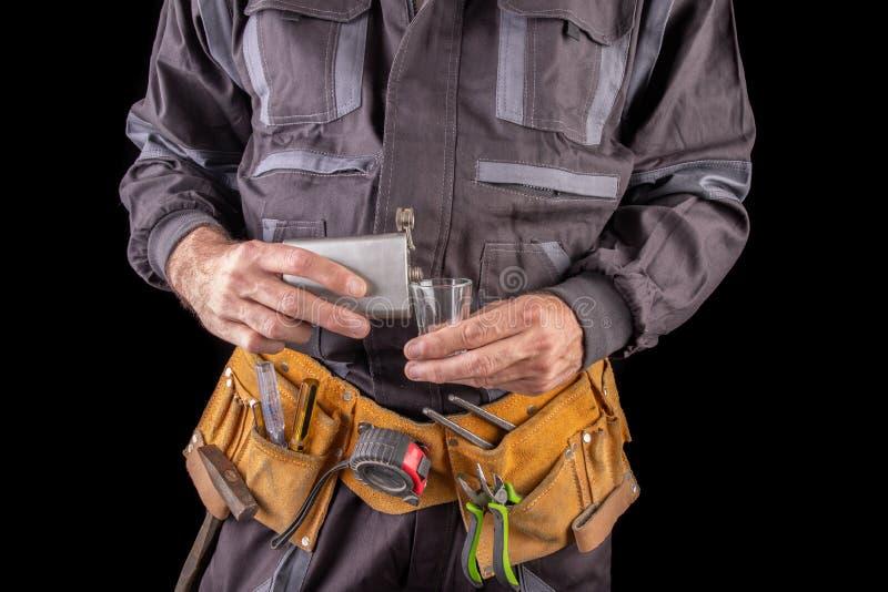 防护服装和一个烧瓶的一名工作者用伏特加酒 醉酒的工人在工作场所 免版税库存图片