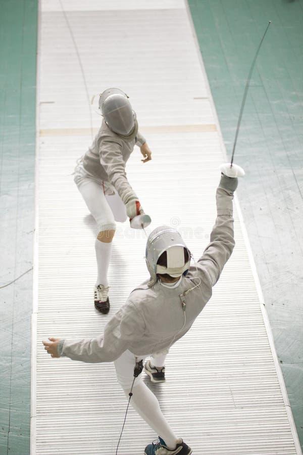 防护服装的年轻击剑者战斗在剑术竞争的 库存照片
