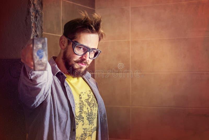 防护玻璃的恼怒的有胡子的工作者拿着在他前面的一把重的锤子打算教某人教训 库存图片