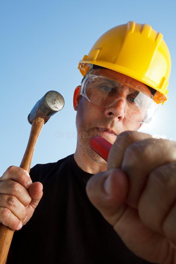 戴防护盔甲和眼镜的建筑工人击中有锤子的凿子 免版税库存照片