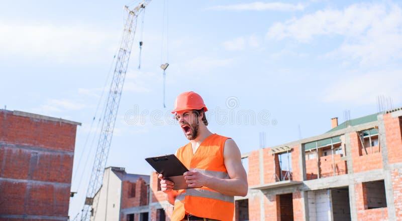 防护盔甲立场的人在从红砖做的大厦前面 人橙色背心和盔甲运转在 免版税图库摄影