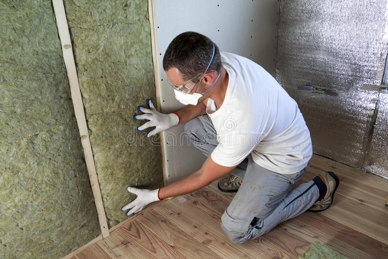 防护眼镜和人工呼吸机绝缘的矿毛绝缘纤维绝缘材料的工作者在未来房子墙壁的木制框架寒冷的 免版税库存照片
