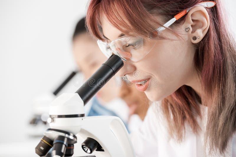 防护眼镜的年轻科学家与显微镜一起使用在化工实验室 免版税库存图片