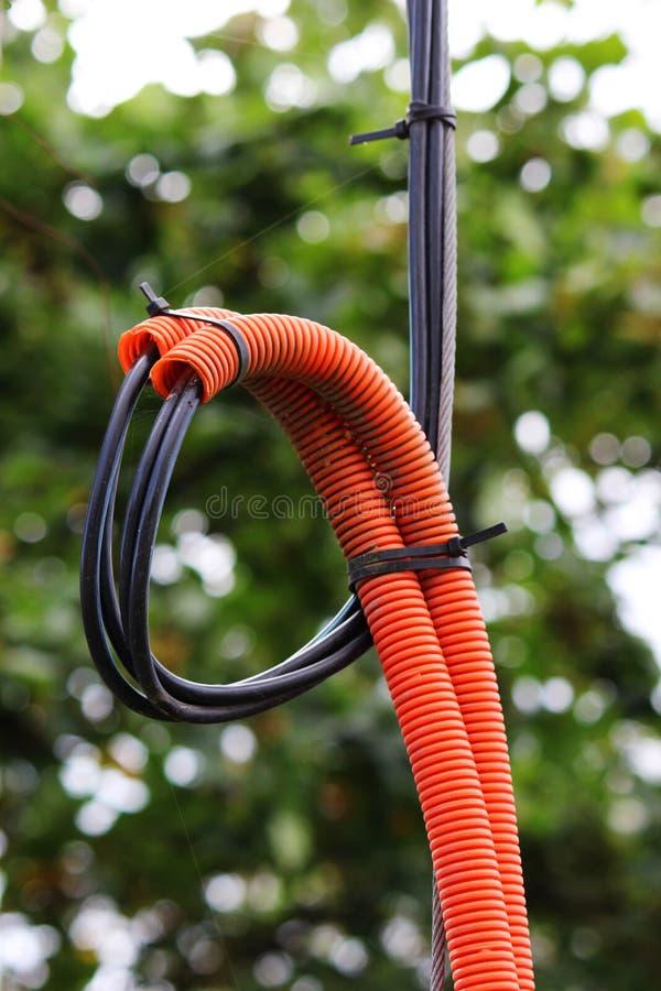 防护PVC使有里面电缆的管子成波状 在火的情况下,火出去和压缩 图库摄影