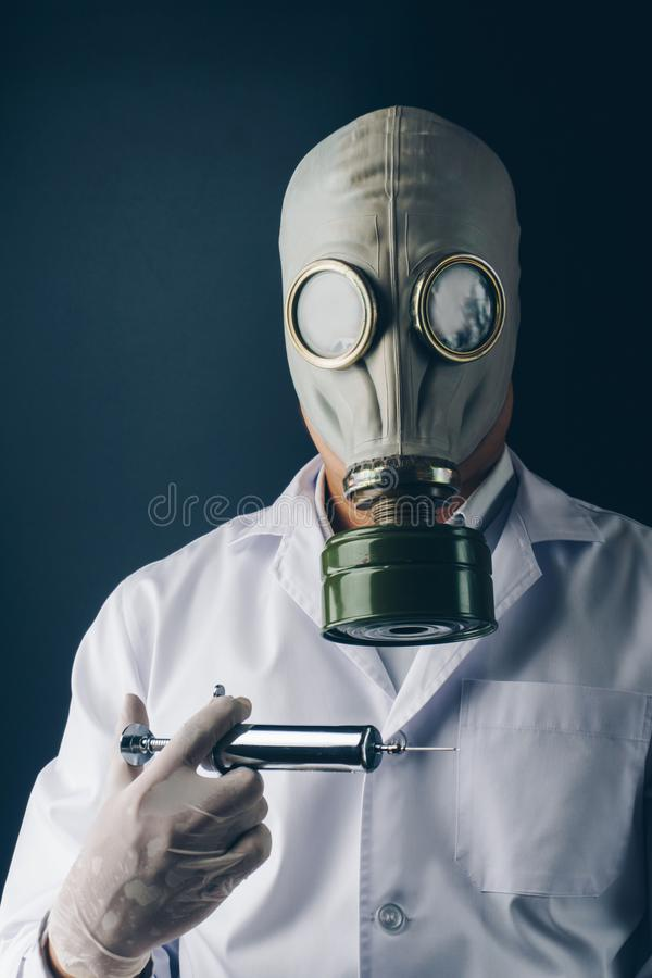 防毒面具的一位可怕医生有一个大不锈钢注射器的 库存图片