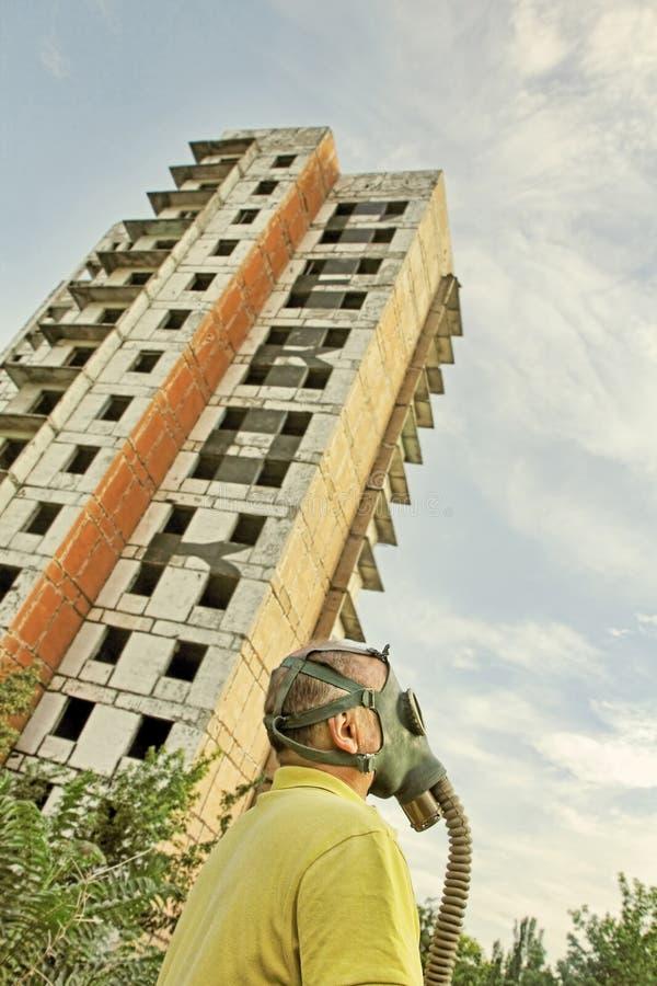 防毒面具的人在被毁坏的大厦和蓝天背景 免版税库存照片