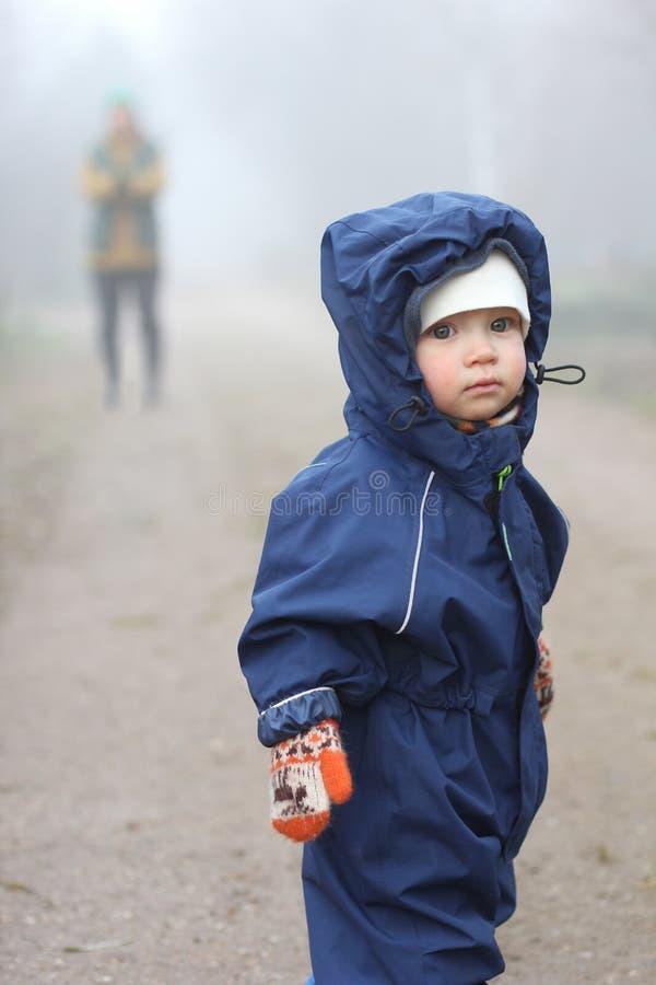 防水衣服的逗人喜爱的小孩男孩在雾站立 库存照片