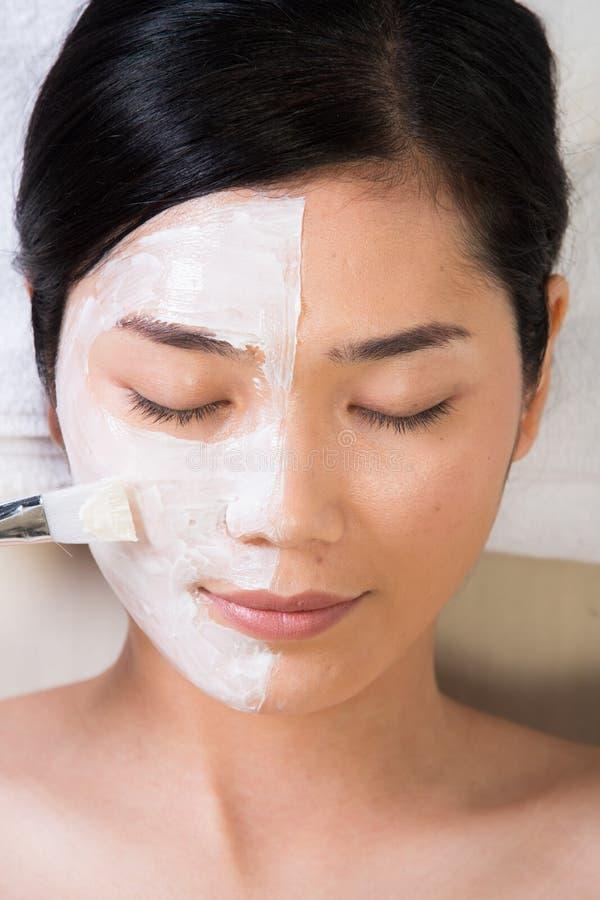 防皱通过应用在面孔的刷子自然奶油 免版税库存图片