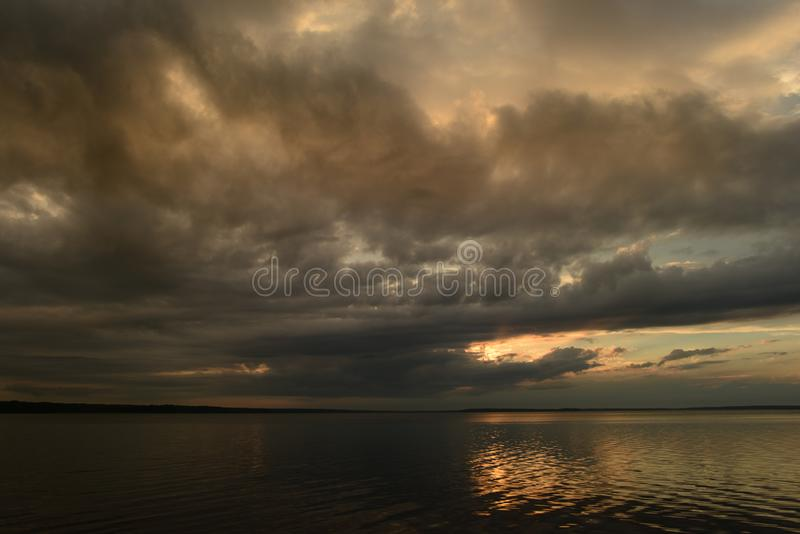 阳光从一乌云的在湖的安静的水表面的上多云天空 库存照片