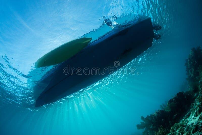 阳光和小船在礁石上 图库摄影
