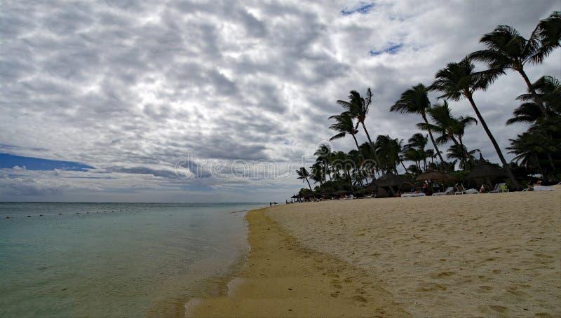 阳光明媚的一天里,人们在毛里求斯印度洋边缘的Flic en Flac公共海滩上散步,那里种着热带树 库存图片