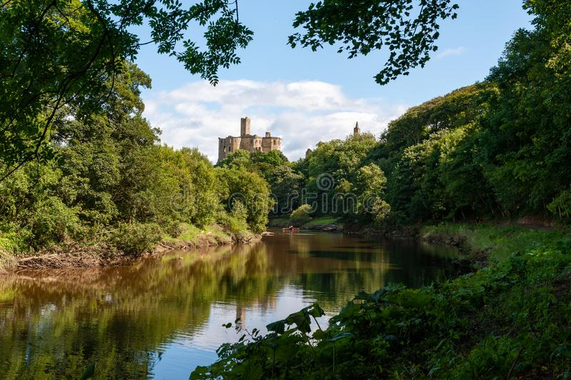 阳光明媚的一天,位于英国诺森伯兰郡莫佩斯的沃克沃思城堡和科凯河 库存图片