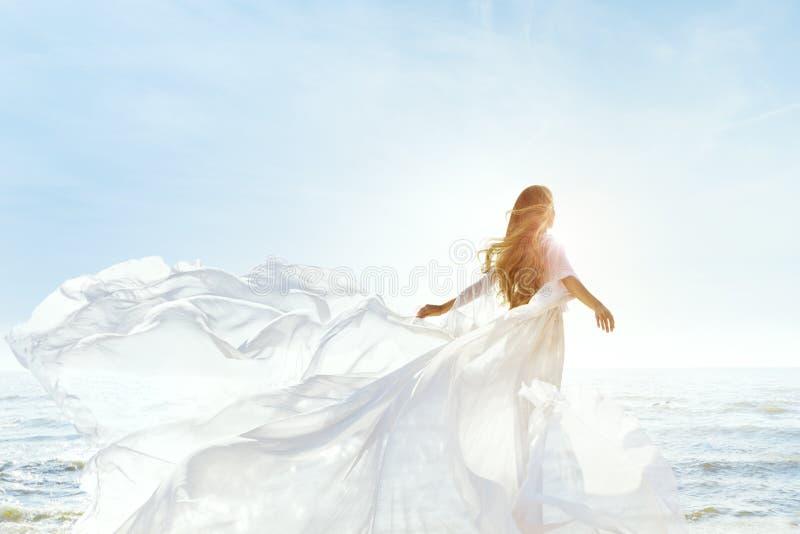 阳光明媚的海滩上女人,穿着白色飘扬的裙子,后视时尚模特,丝绸布在风中摇曳 免版税库存照片