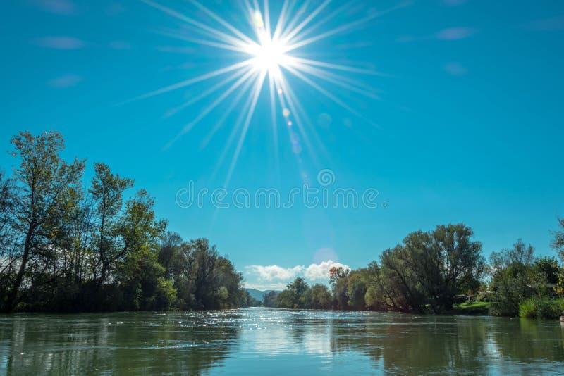 阳光沐浴的河 免版税库存图片