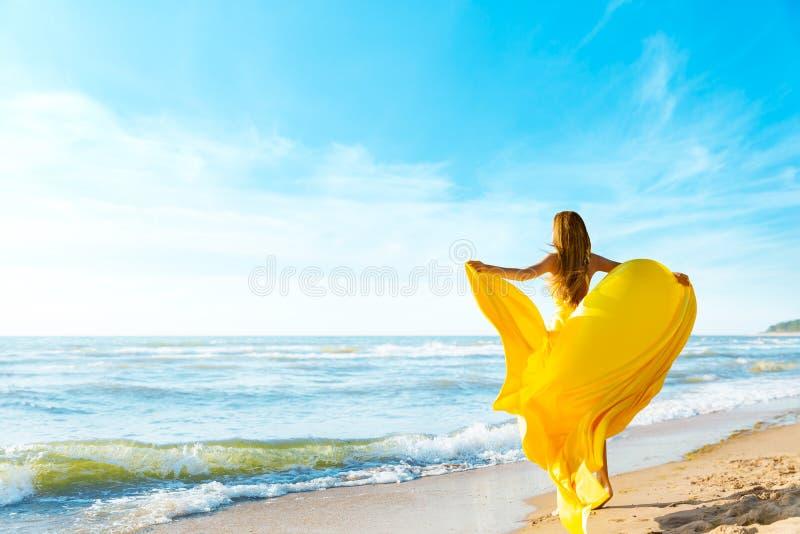 阳光海滩上的女人,穿着黄色飘扬的服装,后视时尚模特,丝布在风中摇曳 库存照片