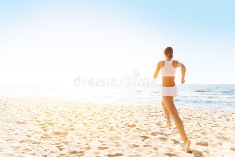 阳光海滩女跑背景白色运动服慢跑女 免版税库存图片