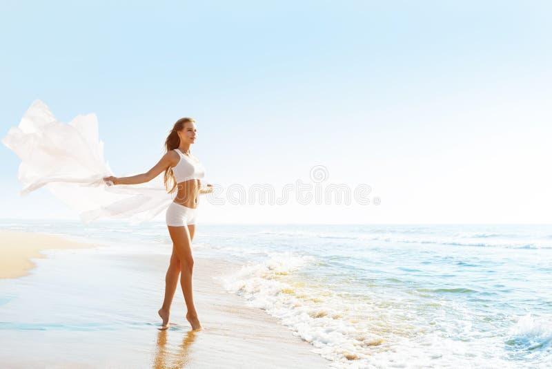 阳光海滩时尚模特白色性感运动服女装风口飘布 免版税库存图片