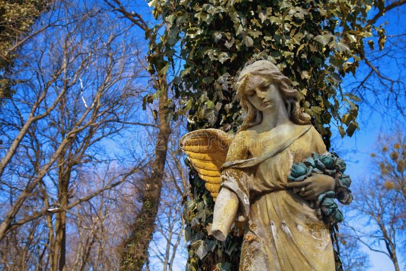 阳光照亮的金黄天使雕象庄严看法  库存照片