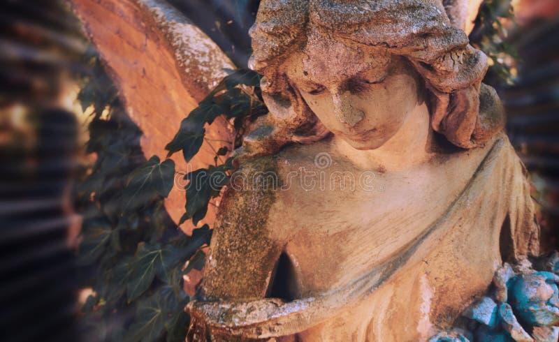 阳光照亮的金黄天使雕象庄严看法  免版税图库摄影