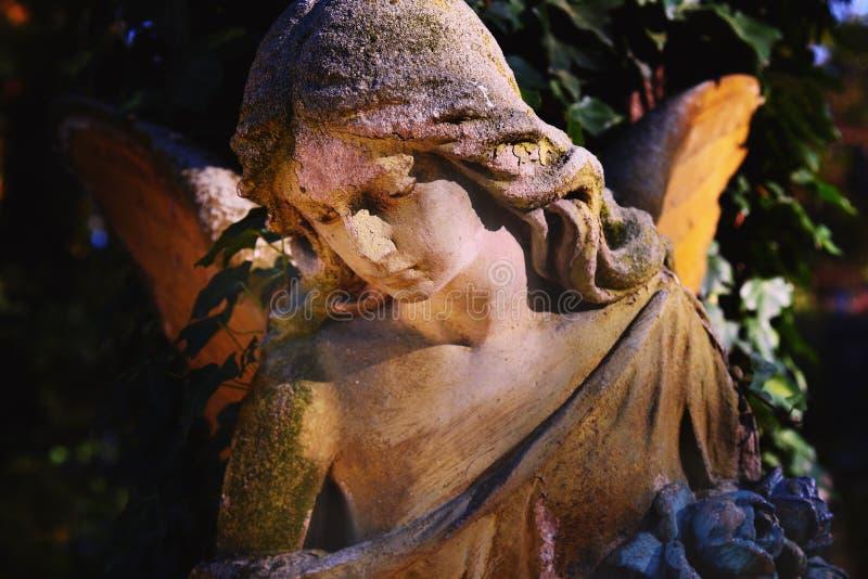 阳光照亮的金黄天使雕象庄严看法  图库摄影
