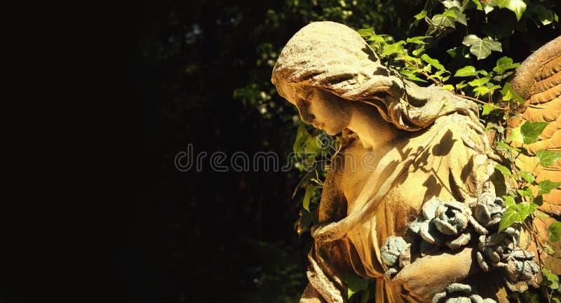 阳光照亮的金黄天使雕象庄严看法  免版税库存照片