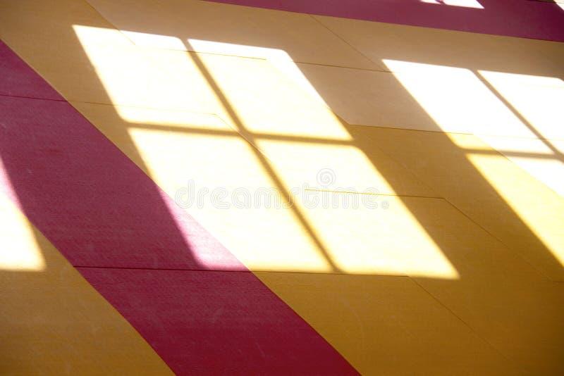 阳光的阴影亮光通过窗口的正方形在地板上的 橙色阳光口气腾出空位感到温暖并且有 库存照片