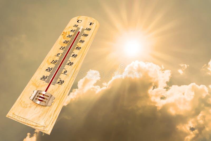 阳光背景显示高温的温度计 免版税库存照片